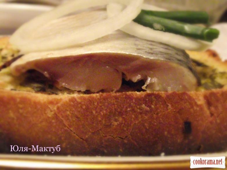Оселедець із зеленим маслом на білому хлібі