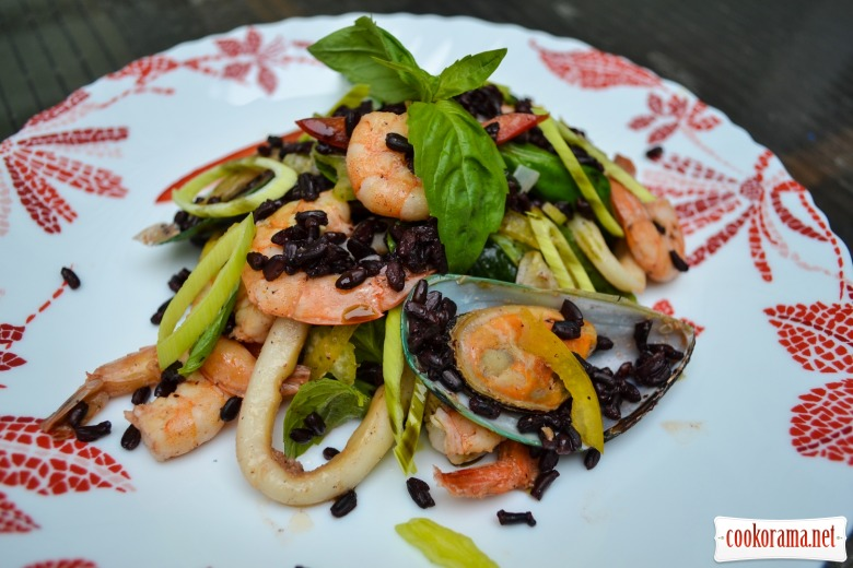 Seafood salad with rice Nerone, seasoned with pumpkin oil
